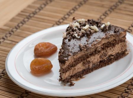 frutas secas: Rebanada de pastel de chocolate con guarnición de frutos secos en un plato con frutas secas.