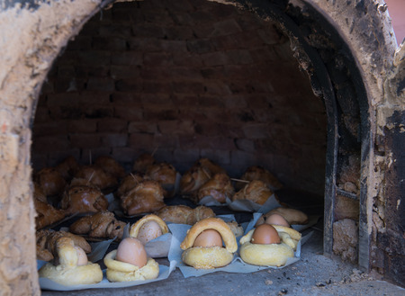 Easter eggs coverd with bread and Cypriot cheese pies cooked  on a clay oven. Stock Photo