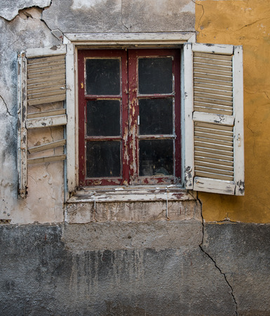 desolation: Closed broken window on a colorful wall. Concept of abandonment and desolation.
