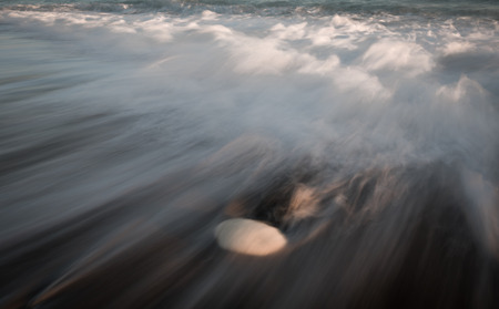 waves  pebble: Sea waves crashing into the shore  and flowing above a white pebble. Long exposure photography