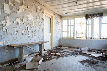 open windows: Interior of a damaged abandoned room with broken open windows and dirt on the floor