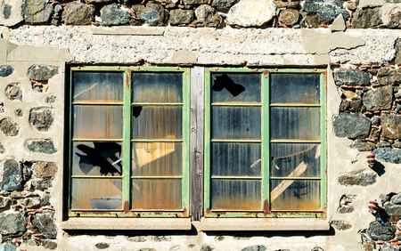 stoned: Closed metal windows on a stoned wall with broken glass from an abandoned building.