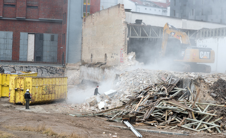 deconstruct: Male workers and high power bulldozer  demolishing  a building at Berlin Germany
