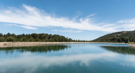 cyprus tree: Water reservoir dam with forerst tree reflections at Prodromos village  in  Troodos mountains in Cyprus. Stock Photo