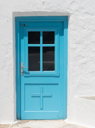 greek islands: Blue traditional  closed  church door on a white wall from the Greek islands if Greece