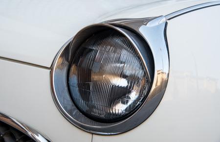 shiny car: Headlight of a shiny vintage white car