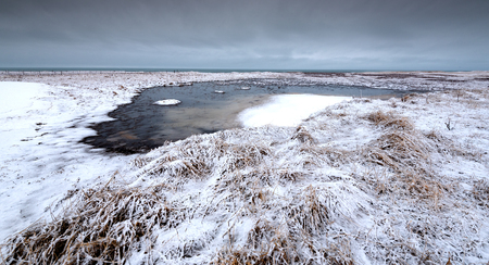 Typical Icelandic dramatic landscape with frozen lake near the Atlantic ocean in Iceland Stock Photo