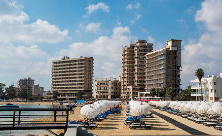 Famagusta, Cyprus - September 15 2016: Palm Beach with beach umbrellas and tourists and the abandoned hotels at Varosha ghost town, Famagusta, Northern Cyprus Editorial