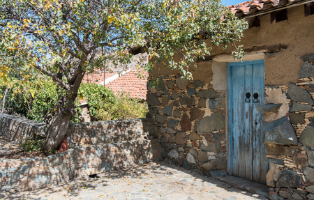 architecture bungalow: Traditional  exterior yard  of a house with a blue wooden door from a village in Cyprus Stock Photo