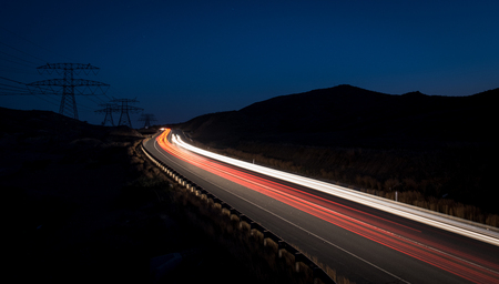headlight: Light trails from cars moving fast late in the evening. Concept of high speed