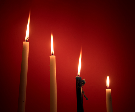 source of light: Holy religious candles burning  creating a mysterious atmosphere. Stock Photo