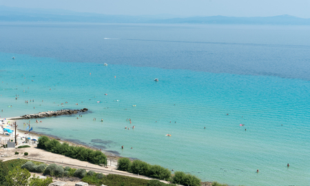 Chalkidiki, Greece- July 26 2017: Panoramic view of famous and idyllic beach of Kalithea with people swimming, resting and enjoying their summer vacations  Kassandra Peninsula in Chalkidiki, Greece