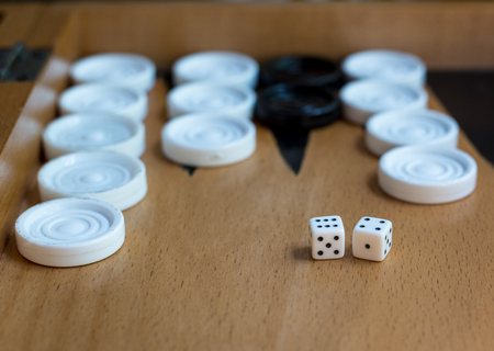 Wooden Backgammon board with white  and black slots and dices Stock Photo