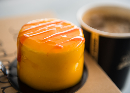 Fresh delicious caramel cake with cream and sweet red syrup on  the top and a cup of coffee
