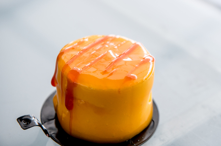 Fresh delicious caramel cake with cream and sweet red syrup on  the top Stock Photo