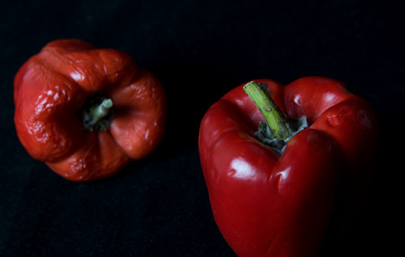 Red mouldy vegetable peppers isolated on a black background