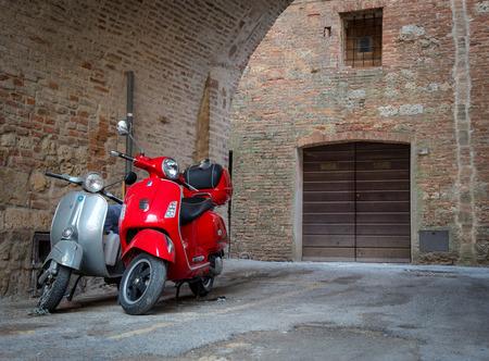 Montepulciano, Italia - 3 de octubre de 2017: motos Vespa vintage rojas y grises aparcadas en las calles de Montepulciano en Tuscana, Italia.