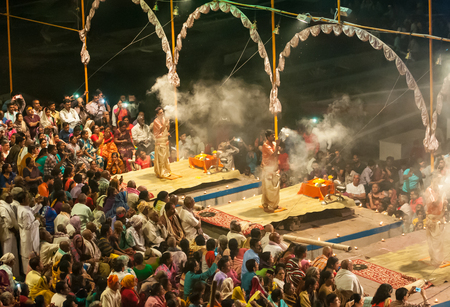 Varanasi, India - March 13 2017: Night prayers from Indian priests with people watching, on the banks of the river Ganges at Varanasi, India