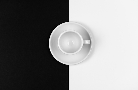 White empty coffee mug resting on a black and white background