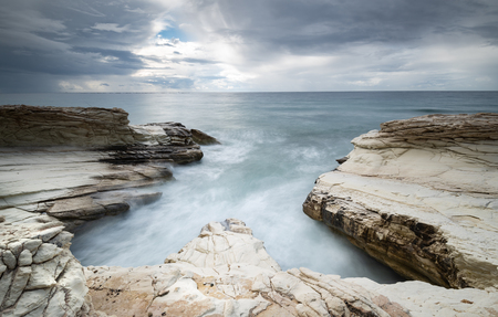Beautiful Rocky coast with white limestones forming wonderful patterns and waves hitting the rocks. Long exposure photography. 免版税图像