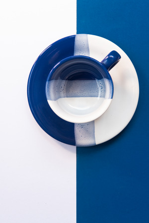 Blue and White empty coffee mug resting on a blue and white background Stock Photo