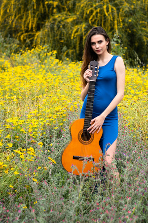 Attractive young caucasian beautiful lady, dressed in blue clothing with a classic guitar in the spring colourful fields. Concept of welcoming Spring