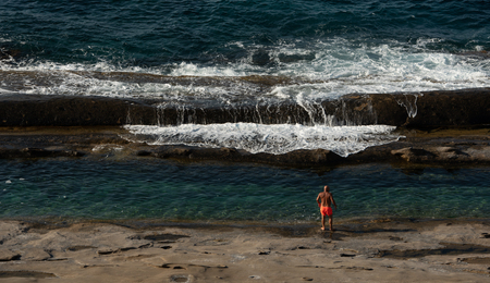 Unrecognised man in orange swimsuit ready to jump in to the beautiful blue sea waters Stock fotó