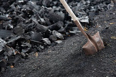 Pile of ready black Charcoal and  a Shovel form a a charcoal manufacturing place in Cyprus