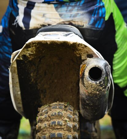 Unrecognized Athlete riding a sports motorbike and muddy wheel on a motocross racing event