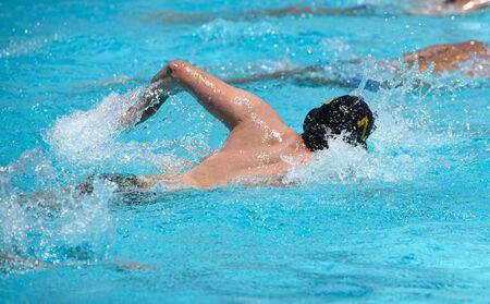 Athlètes non reconnus nageant en style libre et faisant de l'exercice dans une piscine. Banque d'images