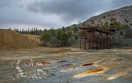 Abandoned copper mine with red toxic water and dramatic stormy cloudy sky at Mitsero area in Cyprus
