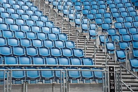 Blue plastic empty stadium or stage chairs in a row