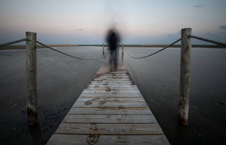 An unrecognised person walking like a ghost at a wooden pier