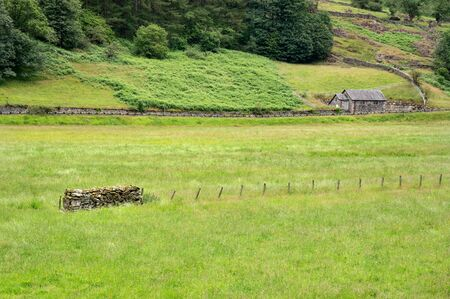 Beautiful wooden cottage house on the picturesque green farmlands at the Lake District area in United Kingdom