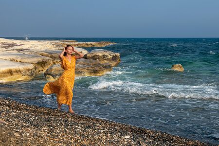 Young beautiful Caucasian woman wearing a yelllow summer dress and and walking on on the beach.