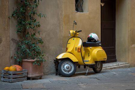 Shiny yellow stylish motorbike outside an Italian house