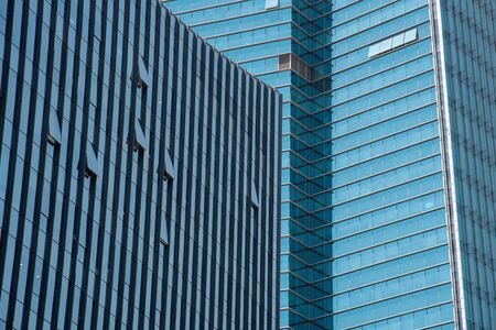 Modern glass skyscraper office building with open windows.
