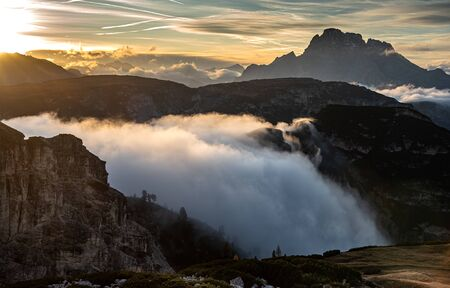 Mountain landscape with fog, late in the evening of the picturesque Dolomites at Tre Cime hiking path area in South Tyrol in Italy.