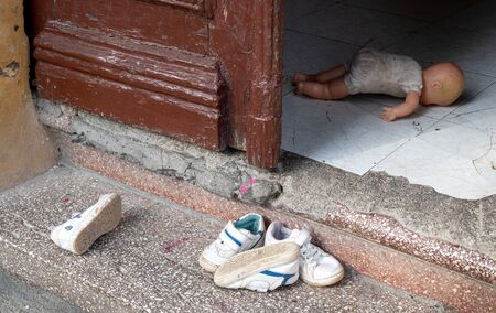 Teenage small used shoes outside the back door entrance of a house.