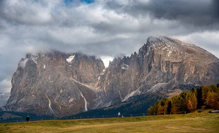 Beautiful mountain landscape with Dolomite rocky peak covered with clouds and unrecognised people hiking  at the at the famous Alpe di Siusi valley South Tyrol in Italy