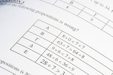 Mathematics problem solving with exam paper questions on a paper and a pencil.