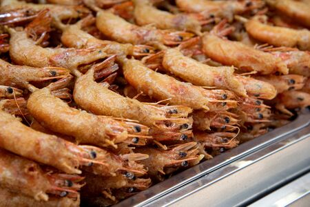 Delicious cooked healthy fresh fried shrimps fish ready to be eaten on an Asian food market