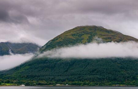 Idyllic mountain landscape with morning early fog covering the peaks at Fort Williams, Glencoe area in the Highlands of Scotland, United Kingdom Banco de Imagens
