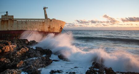 Abandoned ship in the stormy sea with big wind waves during sunset. Stock Photo