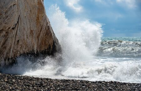 Rocky seashore with wavy ocean and waves crashing on the rocks Aphrodite Rock Paphos area, Cyprus