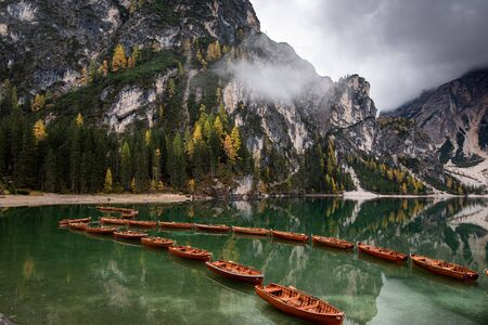 Wooden boats on the peaceful and beautiful lake lago di braies in the italian dolomites, South tyrol, Itlay