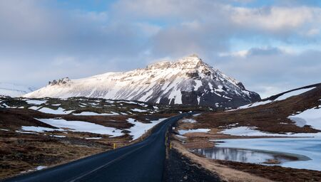 Typical Icelandic snowy nature mountain landscape and empty road near Arnarstapi area in Snaefellsnes peninsula in Iceland
