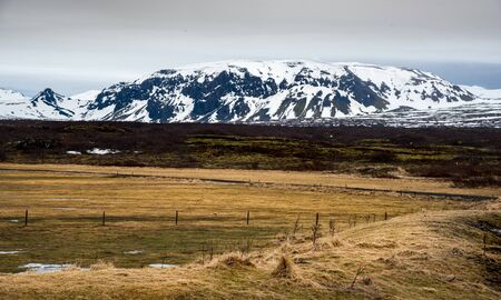 Typical Icelandic dramatic landscape with frozen lake and mountains covered in snow in Iceland Zdjęcie Seryjne