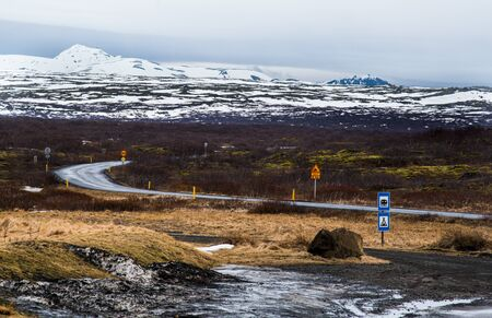 Rural empty road in reykjanes peninsula in Iceland with direction to the mountains covered in snow. Icelandic landscape