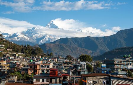 The cityscape of Pokhara with the Annapurna mountain range covered with clouds and snow at central Nepal, Asia